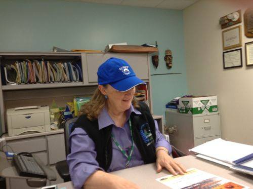 "Kathy Whitman, director of the aquatics department at Seattle Parks is wearing a Rat Island Rowing hat and looking at a ""Save the Oct"" flyer for our campaign"